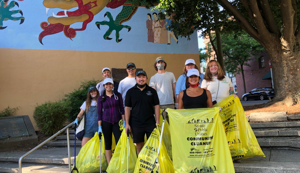 clean up group holding trash bags